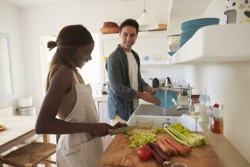 Молодые взрослые пары подготавливая еду для официальныйа обед стоковые фотографии rf
