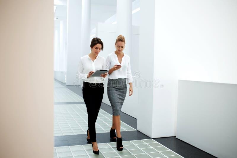 Молодые женские профессиональные сотрудники 2 используя мобильный телефон и сенсорную панель пока идет совместно к конференц-залу стоковые изображения rf