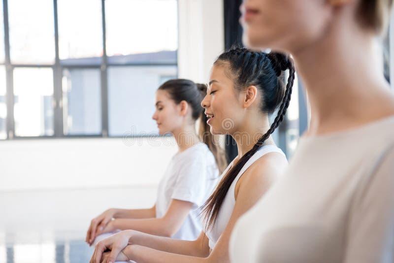 Молодые женщины в sportswear размышляя на занятиях йогой стоковое изображение
