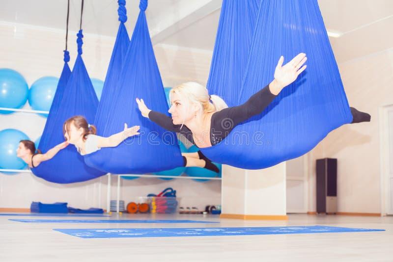 Молодые женщины делая воздушную тренировку йоги или антигравитационную йогу стоковое фото rf