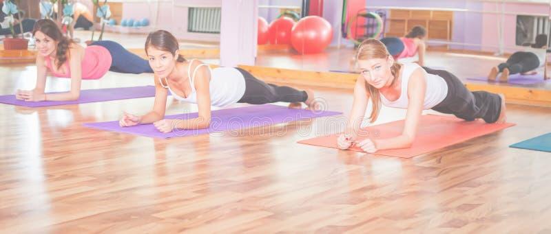 Молодые женщины делая pushups крытые стоковые фото