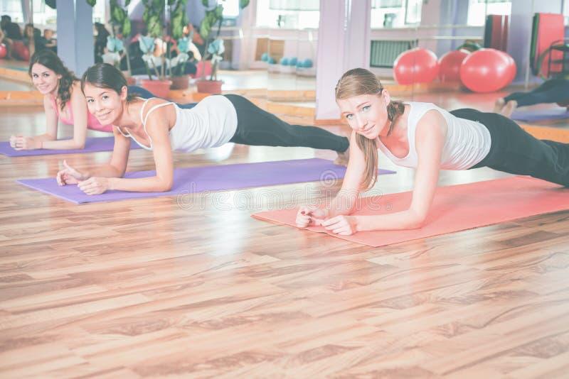 Молодые женщины делая pushups крытые стоковые фотографии rf
