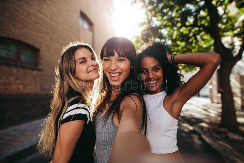 Молодые женщины имея потеху на улице города и принимая selfie стоковые фотографии rf