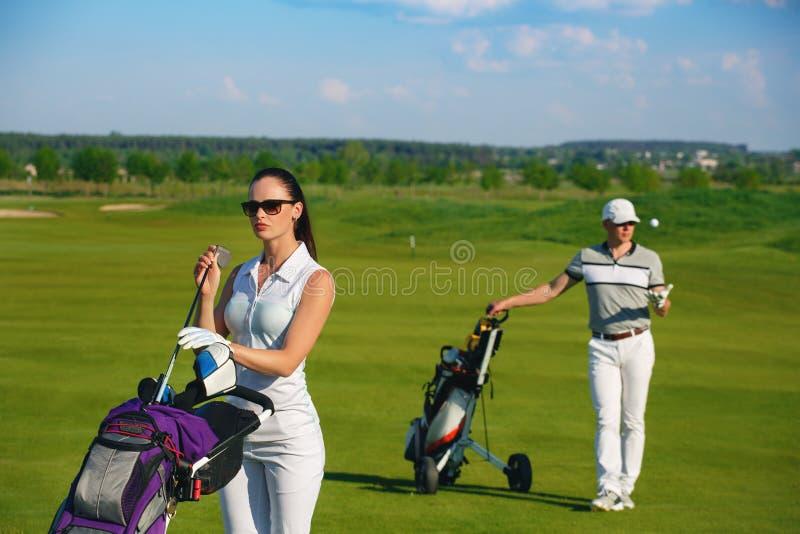 Молодые женщины и люди играя гольф стоковые изображения