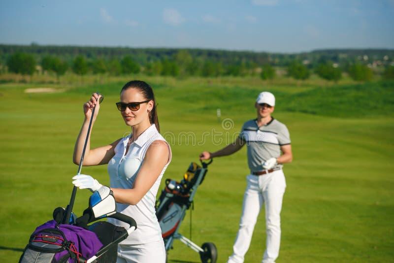 Молодые женщины и люди играя гольф стоковая фотография rf