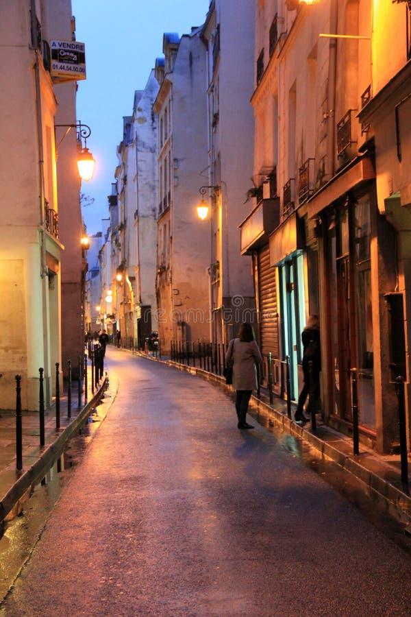 Молодые женщины идя вниз с длинной узкой улицы под мягким освещением, Парижа, Франции, 2016 стоковое фото rf
