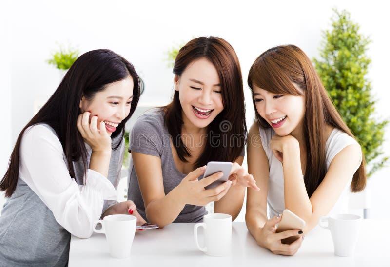 молодые женщины наблюдая умный телефон в живущей комнате стоковые изображения