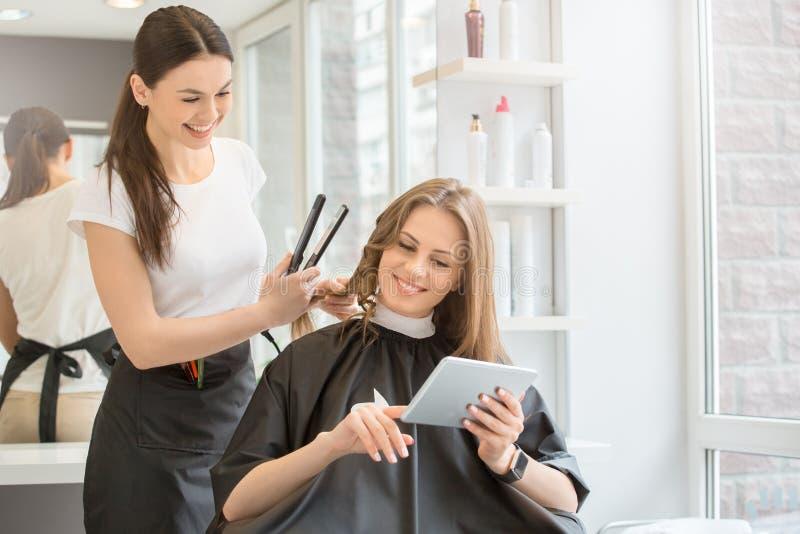 Молодые женщины сидя в стиле парикмахерской красоты стоковое фото rf