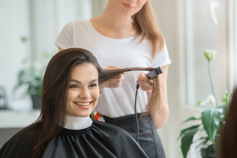 Молодые женщины сидя в стиле парикмахерской красоты стоковая фотография