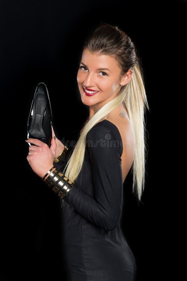 Молодые женщины с длинными волосами в черном платье стоковое фото
