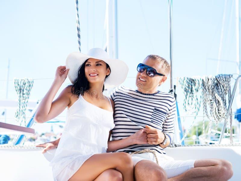 Молодые и счастливые пары ослабляя на каникулах на шлюпке стоковое фото rf