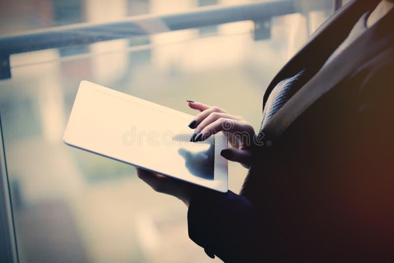Молодые кавказские женские руки держа таблетку и печатая ne текста стоковое изображение