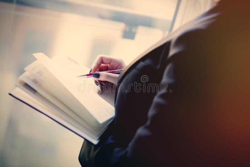 Молодые кавказские женские руки держа тетрадь и писать некоторое стоковая фотография rf