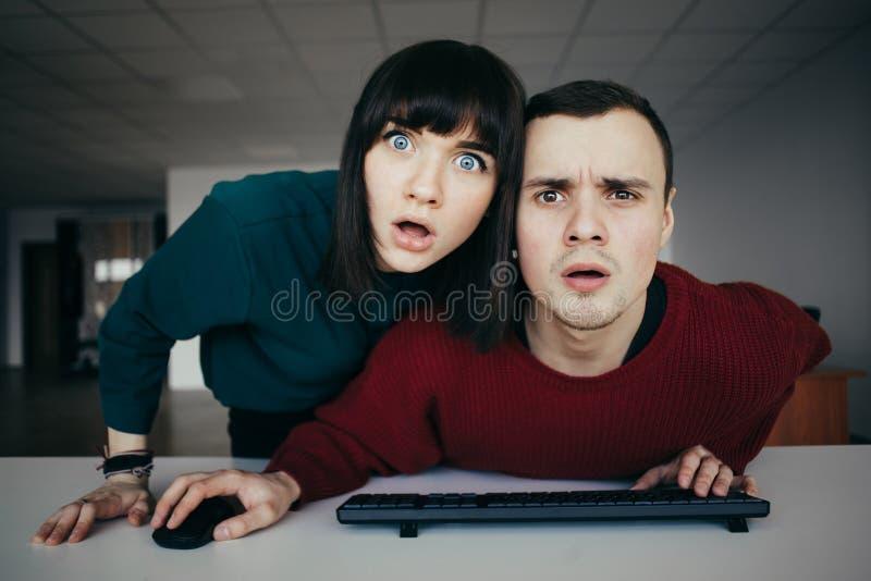 Молодые красивые озадаченные люди смотрят в мониторе компьютера Эмоциональный взгляд на камере стоковая фотография