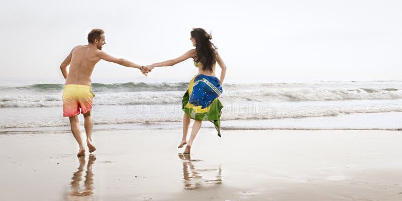 Молодые красивые пары бежать вдоль пляжа с флагом Бразилии стоковые фото