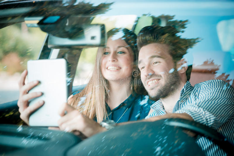 Молодые красивые любовники пар используя таблетку стоковые изображения