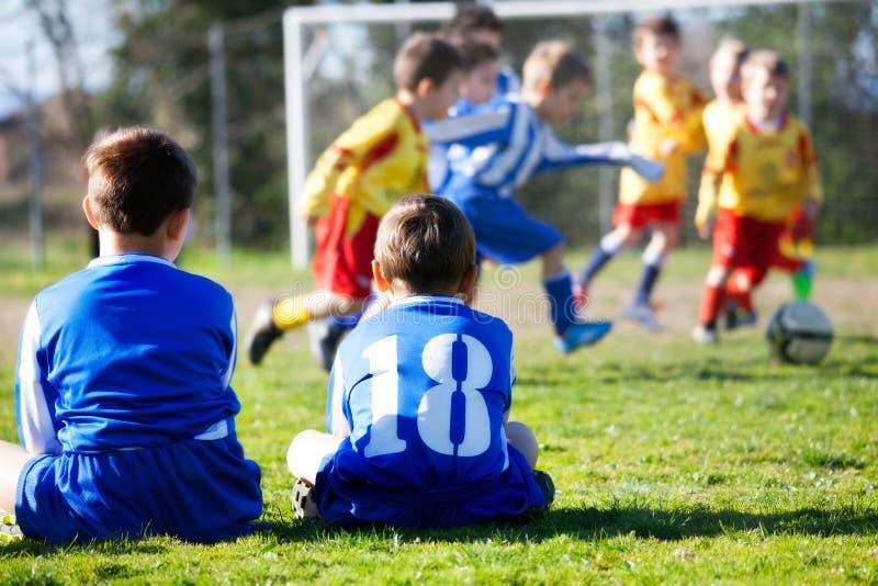 Молодые мальчики в форме наблюдая их команду пока играющ футбол стоковая фотография rf