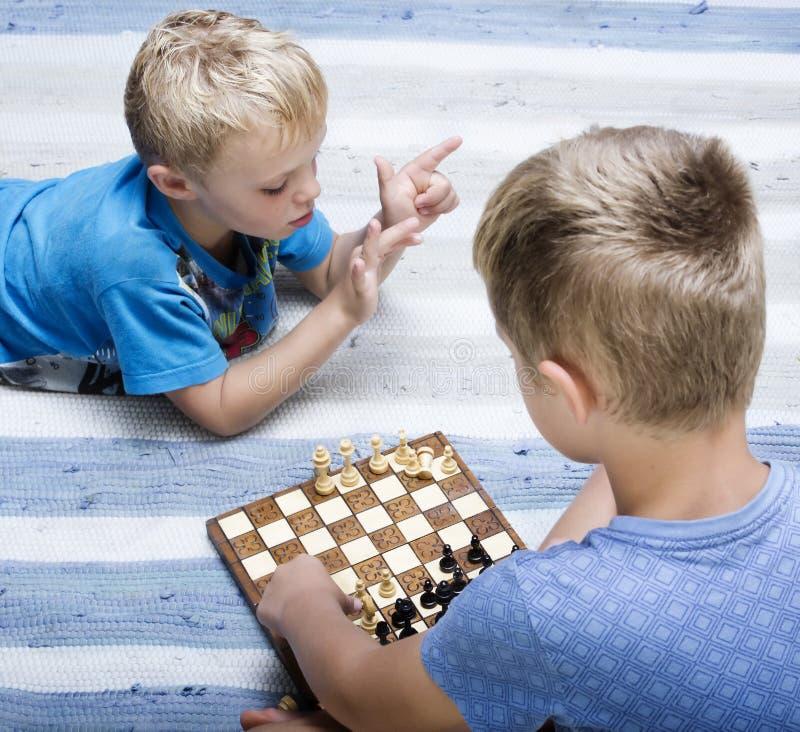 Молодые мальчики играя шахмат стоковые изображения rf