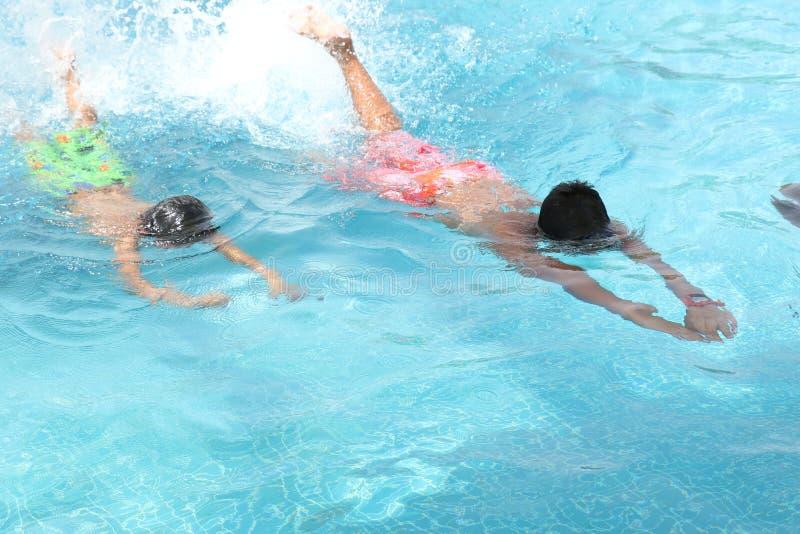 Молодые мальчики наслаждаясь хорошим заплывом в бассейне, DUBAI-UAE 21-ОЕ ИЮЛЯ 2017 стоковая фотография rf