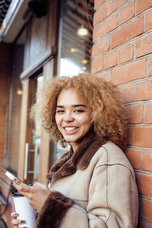 Молодые милые Афро-американские женщины выпивая кофе снаружи в кафе, современной концепции образа жизни бизнес-леди стоковые изображения rf