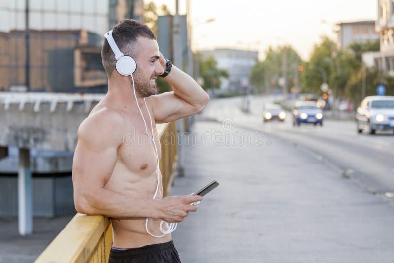 Молодые мышечные спортсмены отдыхают после тренировки пока слушающ к m стоковое изображение