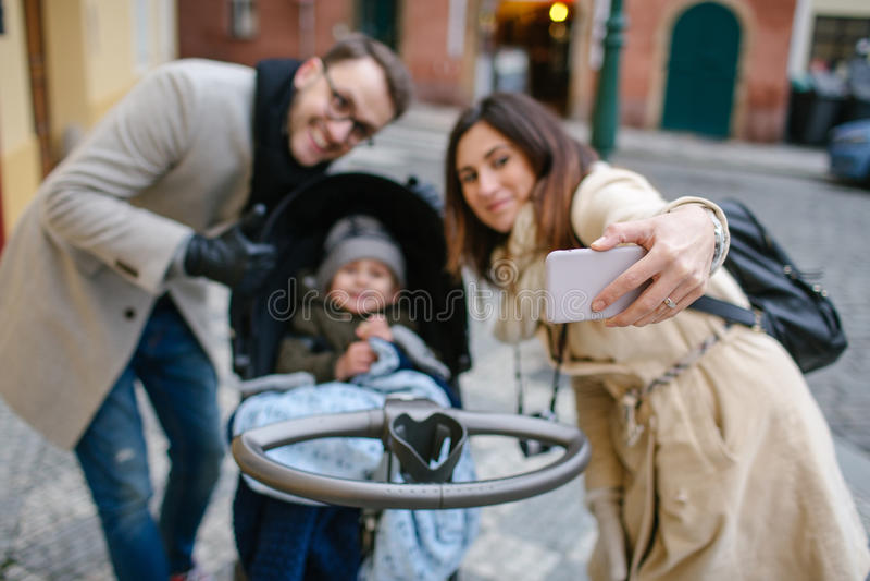 Молодые отец и мать с сыном в детской сидячей коляске outdoors стоковое изображение rf