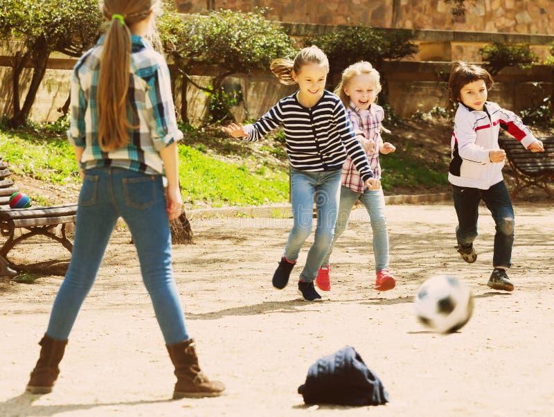 Молодые парни играя футбол улицы outdoors стоковые фотографии rf