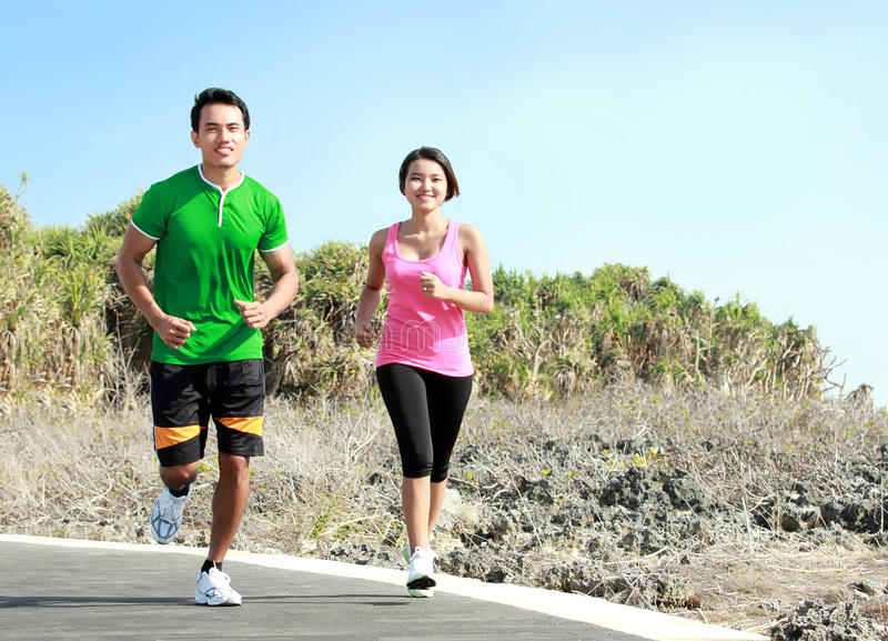 Молодые пары бежать совместно на jogging следе стоковые изображения rf