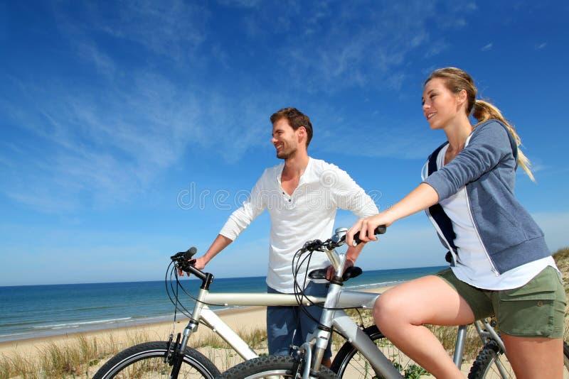 Молодые пары велосипед пляжем стоковое фото rf