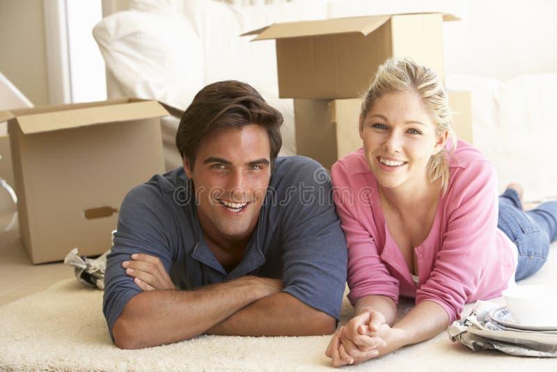 Молодые пары двигая в новый дом окруженный коробками упаковки стоковое изображение rf