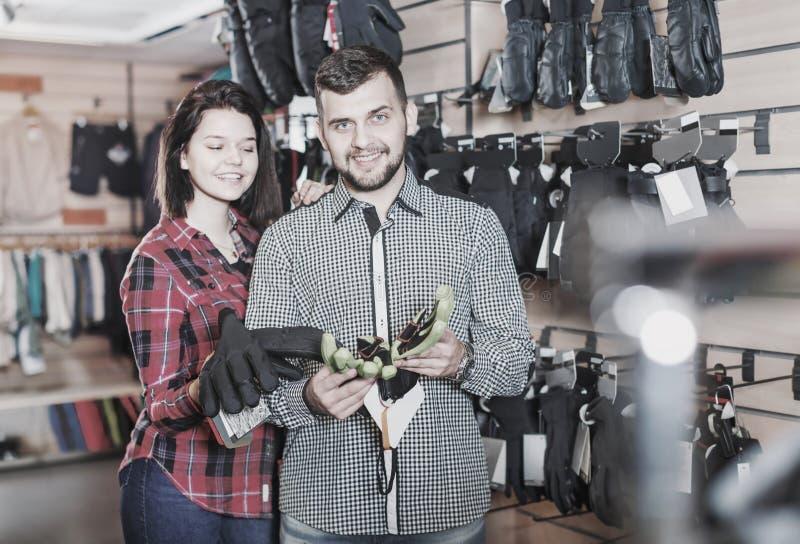 Молодые пары выбирая защитные перчатки стоковые фото