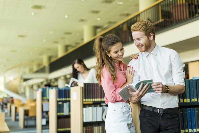 Молодые пары в библиотеке стоковая фотография rf