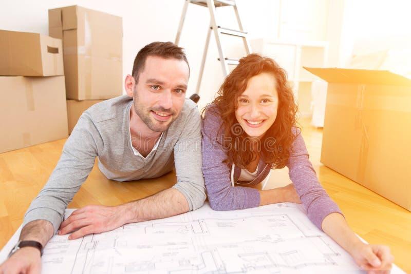 Молодые пары в влюбленности двинули в их новую квартиру стоковое изображение