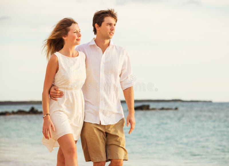 Молодые пары в влюбленности идя на пляж на заходе солнца стоковые фото