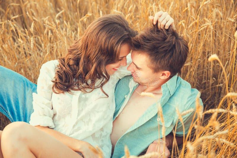 Молодые пары в влюбленности напольной d обнимать пар Молодые красивые пары в влюбленности оставаясь и целуя на поле на заходе сол стоковые фотографии rf