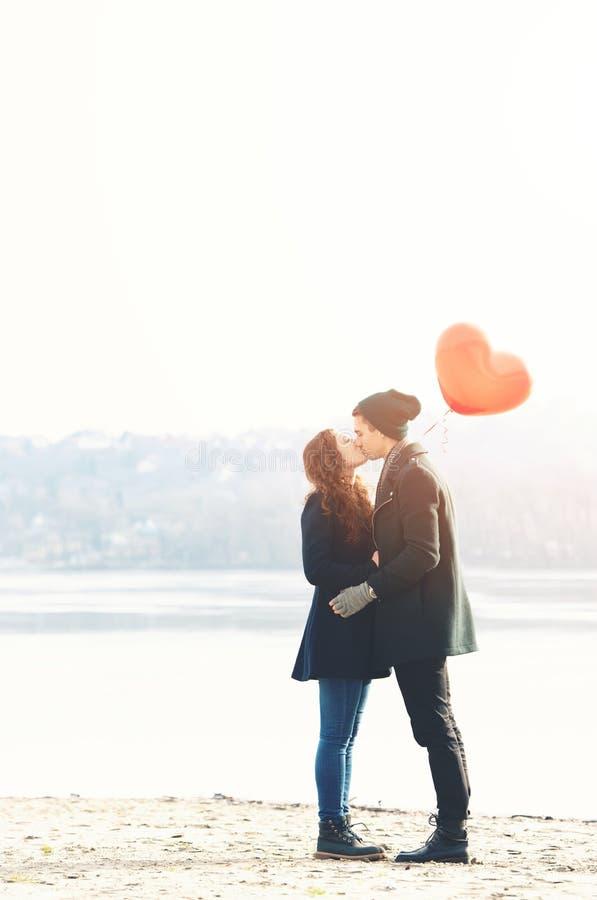 Молодые пары в влюбленности, на береге реки, с красным воздушным шаром стоковая фотография