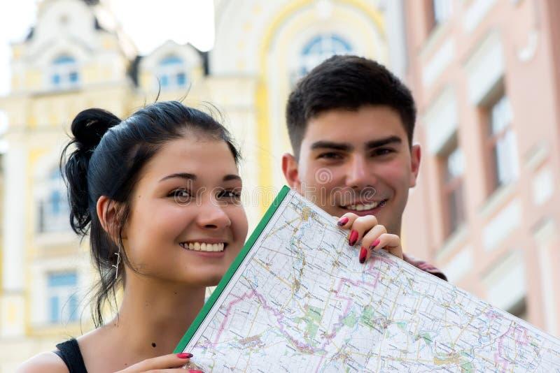 Молодые пары в городке с touristic картой стоковые фотографии rf