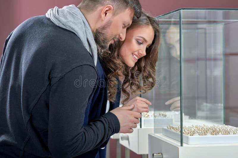Молодые пары в кольцах влюбленности покупая на ювелирном магазине стоковые фото