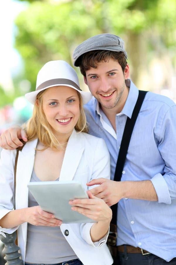 Молодые пары в улицах используя таблетку стоковое фото