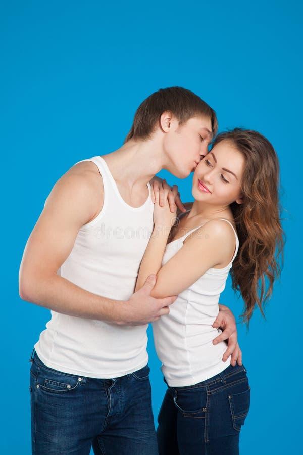 Молодые пары влюбленности целуя и держа один другого в студии стоковые изображения rf