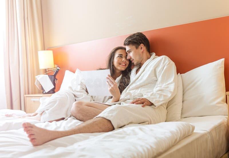 Молодые пары лежа в кровати гостиничного номера стоковые фотографии rf