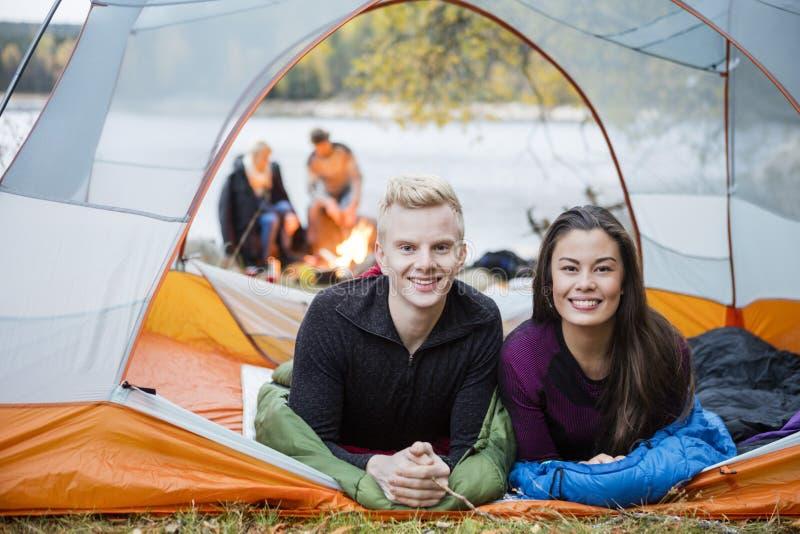 Молодые пары лежа в шатре во время располагаться лагерем берега озера стоковое фото