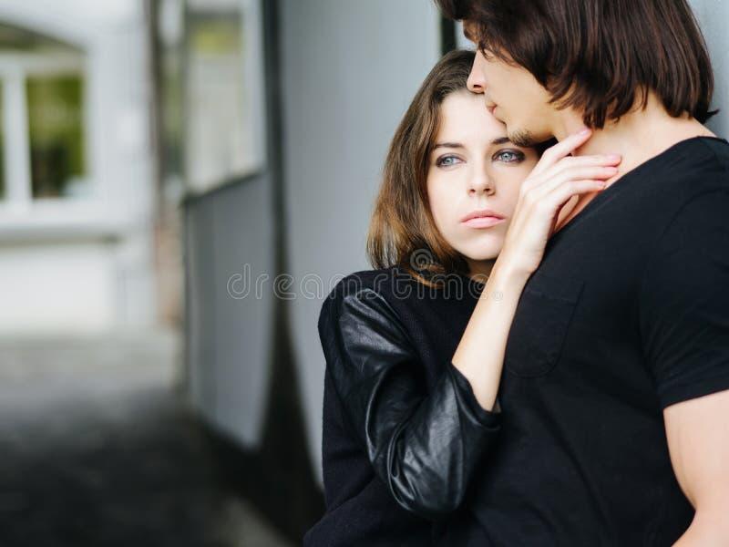 Молодые пары держа один другого в городе стоковая фотография