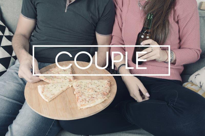 Молодые пары есть пиццу с знаком стоковые фотографии rf