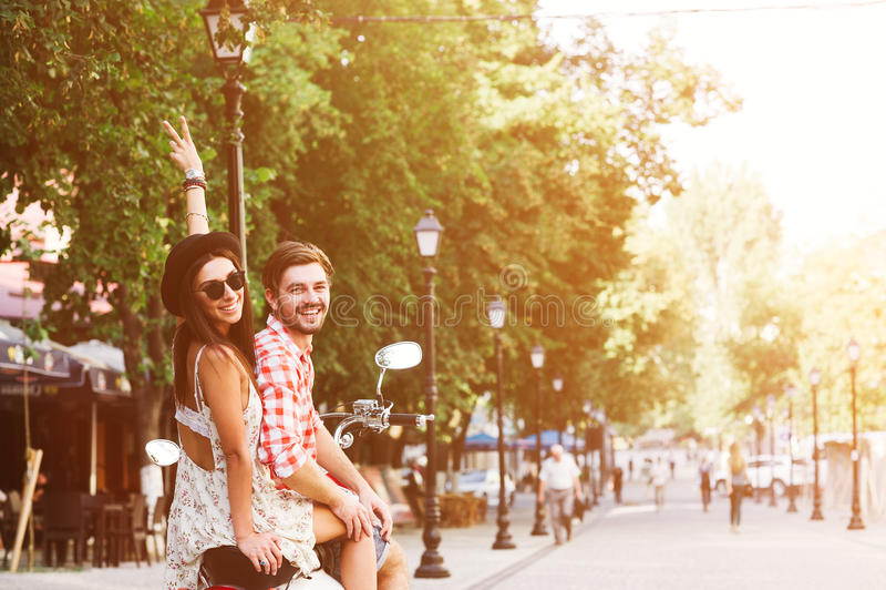 Молодые пары ехать винтажный самокат в улице стоковые фото