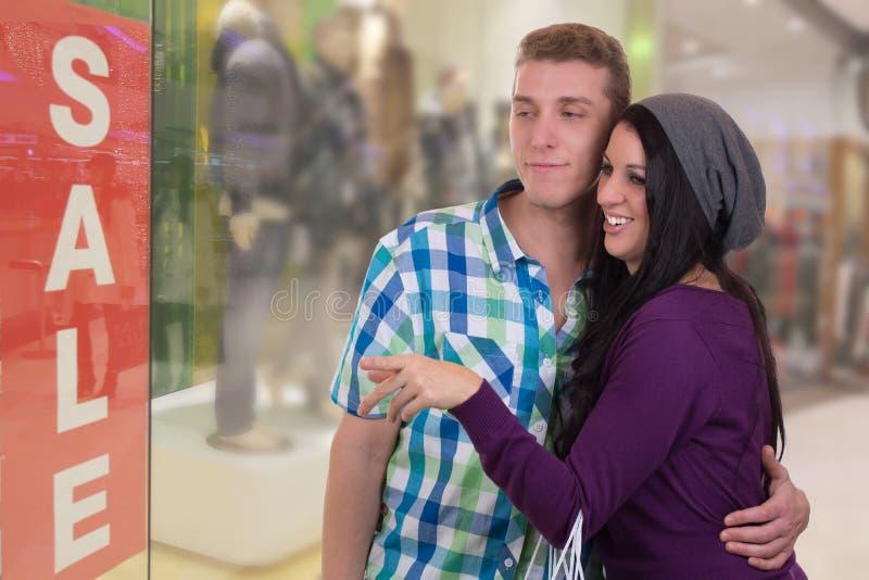 Молодые пары делая покупки окна в моле стоковые фото