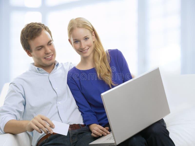 Молодая покупка пар в интернете с кредитной карточкой стоковое изображение