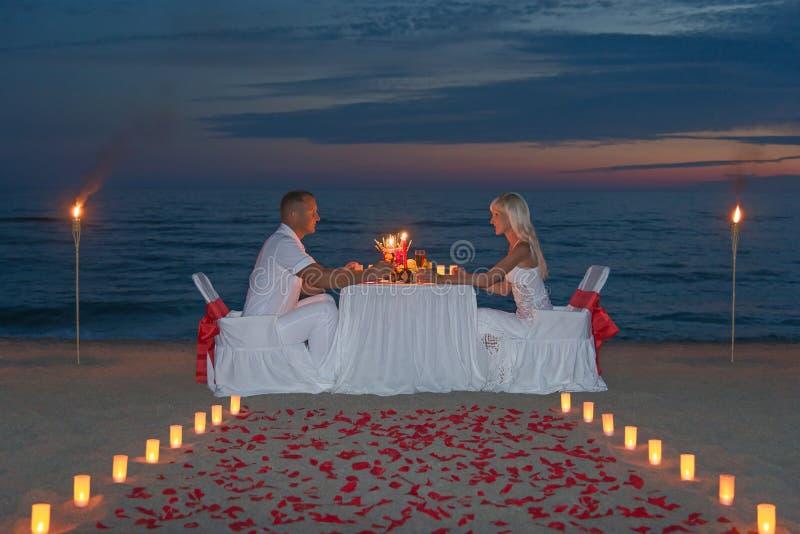 Молодые пары делят романтичный обедающий с свечами стоковая фотография