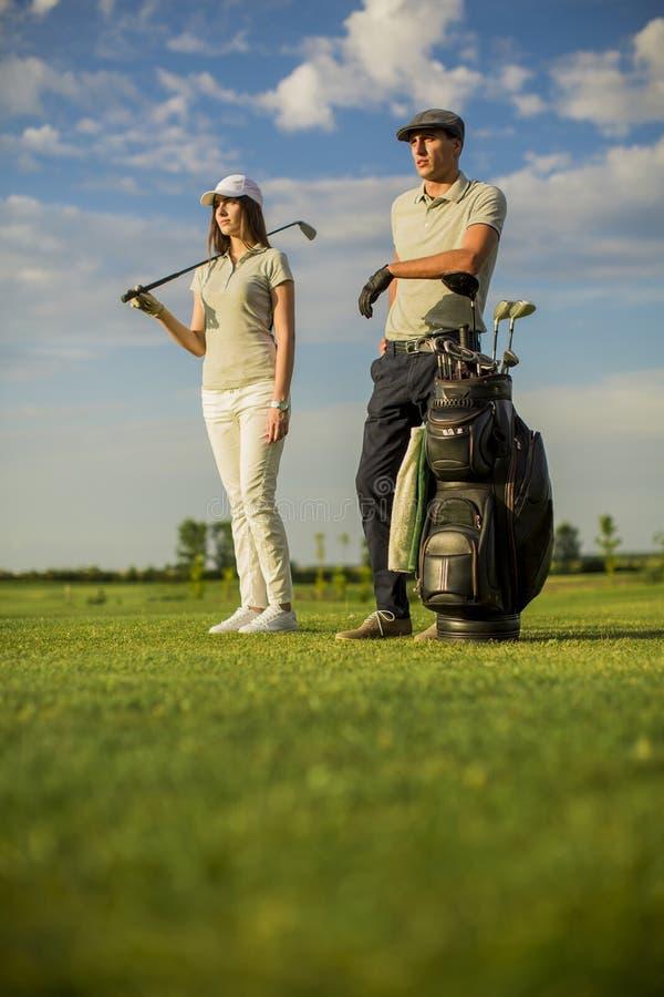 Молодые пары играя гольф стоковые изображения