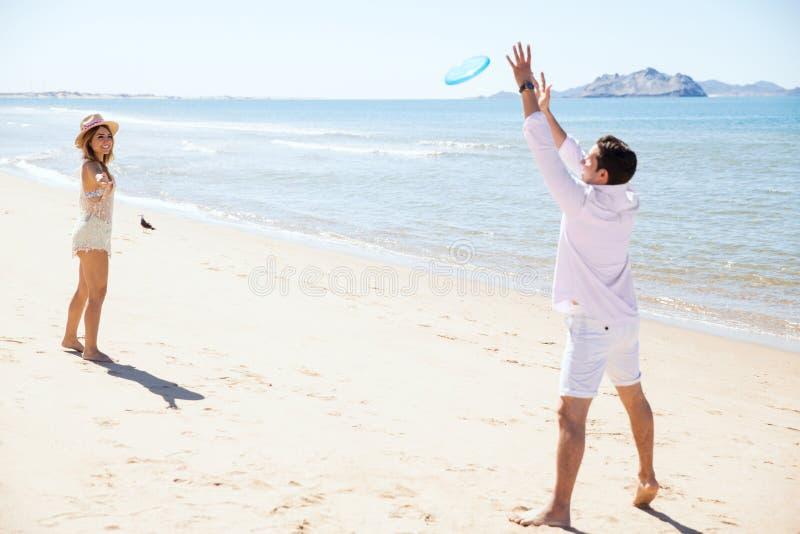Молодые пары играя с диском летания стоковые фотографии rf